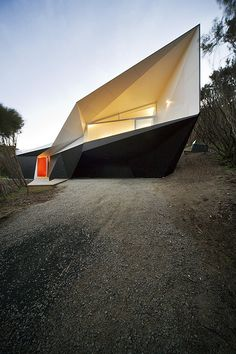 Klein Bottle house by McBride Charles Ryan. Sharp lines form this structure into a abstract geometric shape. The white window contrasts with the black base.
