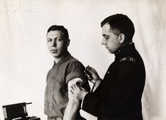 An army surgeon vaccinates a new recruit against typhoid fever.