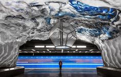Underground art: Stockholm's colourful metro stations. A woman stands on the platform of Tekniska Högskolan as a train rushes by.