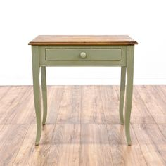 This rustic farmhouse console table is featured in a solid wood with a distressed light olive green paint finish. This small desk is in good condition with curved legs, 1 drawer and a raw wood table top. Perfect as a large side table! #countryfarmhouse #desks #writingdesk #sandiegovintage #vintagefurniture