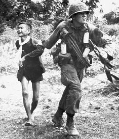 A US soldier grabs a Vietcong suspect as he dashes to a waiting helicopter outside a village near Tam Ky
