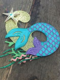 A unique and beautifully detailed cake topper. This number topper will be a wonderful addition to your Mermaid or Under the Sea theme birthday. The number is made out of glitter card stock with coordinating colors in card stock. Number is topped with a real starfish Topper is white on the