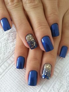 Metallic dark blue nail art design with gold designs. The nails are designed in predominantly blue shades while there is one with gold glitter highlights that stands out from the rest of the nails.
