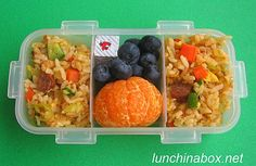 Contents of preschooler lunch: Tangerine, blueberries, cheese cubes and kimchi fried rice with zucchini, carrots, carnitas, and cocktail sausages