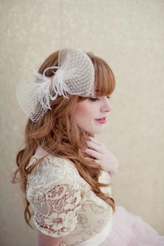 A bow and ostrich feather hair piece compliments a vintage lace wedding dress.