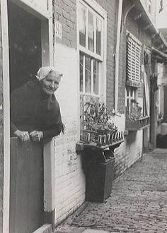 Werfstraat, slopje nr. 142; op de voorgrond een Scheveningse vrouw geleund over haar onderdeur 1930 #ZuidHolland #Scheveningen