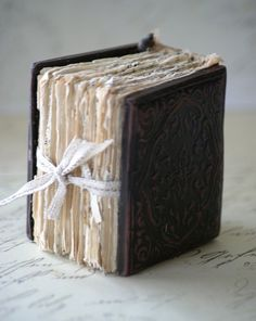 "This book is modelled on an antique daguerrotype photo case from the 1800's. It is made from polymer clay, painted and aged.  The paper signatures are made up from various vintage text book papers.  This books measurements are approximately 3' in height and 2 1/2"" wide."