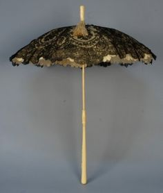 IVORY HANDLED FOLDING PARASOL with LACE CANOPY, 19th C. The handle having floral carving with shield and fancy monogram, matching finial, black Chantilly lace over cream silk canopy.