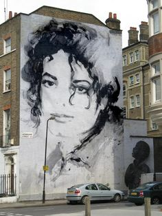 Michael Jackson. I like how the lamp post is his microphone in this picture. Great eye whoever shot this. Notice the same everything except the MJ picture. Somebody is photoshopping.........Check out my Street Art board. I have 3 other ones with different pictures of Johnny Depp,/ Keith Richards, James Dean and Freddie Mercury.