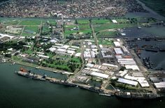 A view of the Naval Base, Subic Bay, with the city of Olongapo in the background. The ships docked at the pier in the foreground are, from right: the oiler USNS HASSAYAMPA (T-AO-145), the guided missile cruiser USS STERETT (CG-31), the guided missile destroyer USS HENRY B. WILSON (DDG-7) and the guided missile cruiser WILLIAM H. STANDLEY (CG-32).   August 1981
