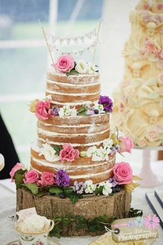 Love this simple  wedding cake love the wooden log/board underneath laden with beautiful flowers.