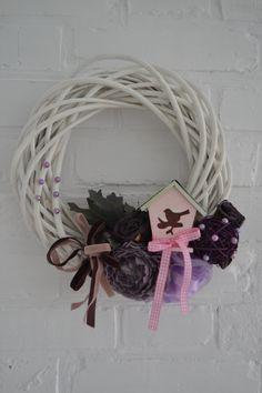 Subtelny, biały, wiklinowy wianek wykonany w kolorystyce różu i fioletu. Dominującym elementem dekoracyjnym jest uroczy drewniany domek. Całość dopełniają śliwkowe kwiaty oraz dekoracyjne wstążki i korale. Średnica ok. 33 cm.