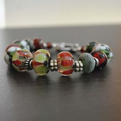 Etsy listing at https://www.etsy.com/listing/163246754/christmas-lampwork-bead-bracelet-red-and