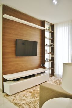 Sala pequena tem painel e sofá com pouca profundidade.