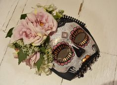 Handmade Día de Muertos skull mask. Paper Mache base with hand painted decoration, pink and white wild flowers, green leaves, black lace, dangling, beaded teeth and pink broach. Black satin ribbon tie. Every mask is handmade and hand painted. The jewels and broaches are collected from vintage shops and markets. Much of the materials are re-used and recycled, as is the packaging. Shipping Details: Guaranteed dispatched within 1-3 days of purchase. I try to dispatch within 24 hours when...