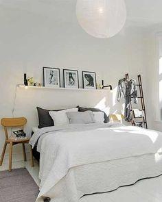 une tête de lit simplissime dans une chambre blanche avec cadre photo sur étagère