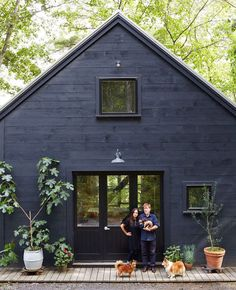 Charming cottage with black horizontal siding with smaller openings.