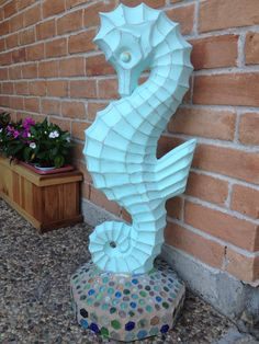 From a simple concrete statue to front porch art! Used concrete paint and sanded the seahorse defining edges. Glass tiles/ flat-backed marbles added to the base. Grouting was the hardest part!
