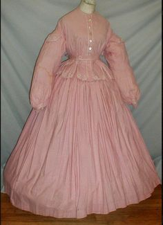 1860's pink cotton print dress, de-accessioned from a museum. bishop styled sleeves decorated with epaulettes. The armscyes are piped. The bodice hemline has a tab styled peplum. The bodice is trimmed with white braiding. It is unlined and has a front button closure. The full skirt is attached to a white camisole top. The skirt is unlined and gauged. separate tie belt is decorated with white braiding.  Bust 36 Waist 32 Front Skirt length 40 Back Length 45 Width 154.