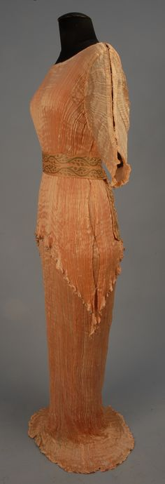 "Side View FORTUNY PEPLOS GOWN, c. 1920. Pink crinkled silk with attached short sleeve tunic, the bottom curving toward open side seams trimmed in silk cord and joined at intervals with blue Murano glass beads, matching trim on sleeves and tunic bottom, separate pink silk sash with metallic stenciled design. Sash and seam tape stamped ""Fortuny Dep"""