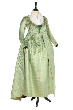 A rare brocaded satin pregnancy robe, 1790s. the pale green silk sprigged overall with ivory and peach trefoils tied with tassels.