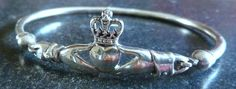 A Vintage sterling silver Irish Claddagh style bangle/bracelet. The bangle has a lovely central Claddagh design. The fastening for the bangle is a latch hook closure disguised as part of the central knot. A stunning piece of Irish themed silver jewellery.
