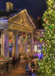 Boston's Quincy Market aglow in colorful holiday lights and Christmas tree with shoppers hustling about trying to finish up on last minute Christmas shopping. Prints starting at $32.00 #Boston #FaneuilHall #QuincyMarket