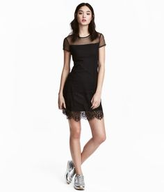 Black. Short dress in patterned mesh with wide lace trim at hem. Opening at back of neck with button and short sleeves. Partly lined in jersey.