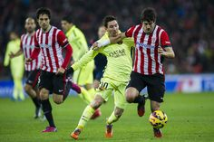 Lionel Messi of FC Barcelona duels for the ball with Mikel San Jose of Athletic Club during the La Liga match between Athletic Club and FC Barcelona at San Mames Stadium on February 8, 2015 in Bilbao, Spain.