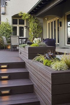 Contemporary deck with raised beds and French doors by Angela Sarmiento. Planters constructed of the same wood used for the deck tie this backyard garden look together. #deck #patio #landsapingideas #raisedbeds