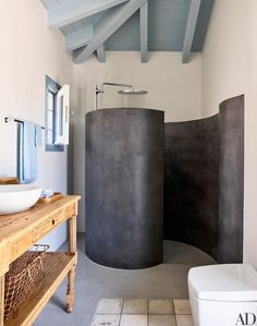 Architect Nikos Moustroufis and designer Isabel López-Quesada created a chic Greek-island compound for an Athens-based couple and their close-knit family. The poolhouse's coiling shower enclosure is fashioned of tadelakt, a waterproof Moroccan plaster; the showerhead is by Grohe.