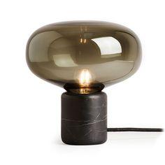 Karl-Johan Table Lamp – en bordslampa formgiven av den unga danska designen Signe Hytte för New Works. Som namnet antyder har Hytte hämtat inspiration från skogens svampar under designprocessen. Karl-Johan har en solid bas i rökt ek eller svart marmor som kontrasterar fint mot den mjuka formen och skärmen i glas.