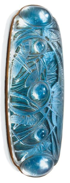 Grasshoppers brooch, circa 1913, consisting of moulded glass and gilt metal, depicting grasshoppers on straw, French assay mark and signed René Lalique.