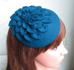 A stunning teal blue dahlia flower hat which has been entirely hand made from individual wool felt petals sewn together to give a natural