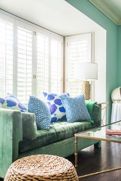 A velvet green vintage sofa sits beautifully in a nook surrounded by plantation shutters. Gold accents and a bold metallic lamp provide warmth to this eclectic living room.Bright blue patterned pillows offer a little contrast to the otherwise monochromatic space. #followback #nailart #nails