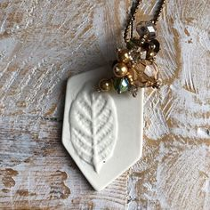 A beautiful porcelain leaf plant tag has been repurposed to become a stunningly simple necklace, with beaded fringe and complimentary colours.