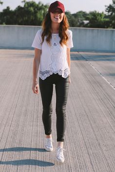 black leather pants, white lace shirt with an interesting hem, maroon cap, and sneaks
