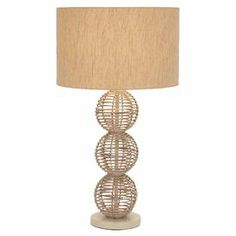 """Rattan table lamp with an openwork base and drum shade.  Product: Table lampConstruction Material: Metal, rattan and fabricColor: NaturalFeatures: Openwork baseAccommodates: (1) 100 Watt medium base bulb - not includedDimensions: 26"""" H x 6"""" Diameter (base)"""