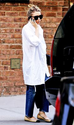 Ashley Olsen wears a white button-down blouse, jeans, ballet flats, and oversized sunglasses