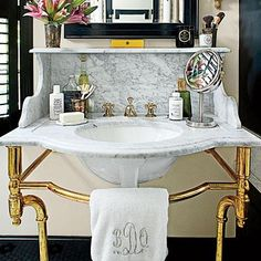 This master bath makes a statement with a pair of handsome Carrara marble-topped washstands with polished brass legs. | SouthernLiving.com
