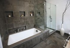 Wall of tile behind tub/shower, cubbies, tub deck extends to shower bench, glass shower walls
