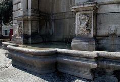 La Fontana di Ponte Sisto. Two dragons carved in the base of the columns spurt water into the basin, as do two lion-heads. The fountain was moved in 1898 when the bed of the Tiber was widened. The Borghese coat of arms dominates everything.