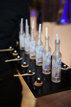 A bread and caviar appetizer is accompanied by a six Snow Queen vodka bottles adorned with straws.