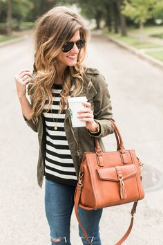 cute fall outfit idea, how to wear a green military jacket styled with black and white stripes,cognac booties and brown leather sole society bag, black and white stripes and utility jacket and coganc booties and brown bag and black aviators