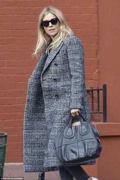 Winter style: Sienna Miller kept out the New York City chill with a baggy charcoal gray ch...