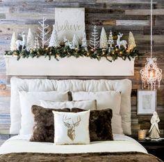 a headboard display with deer, shiny Christmas trees, a fir garland and lights