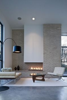 Neutral toned interior living room with modern, leather furniture + over-sized arm lamp and a very sleek fireplace