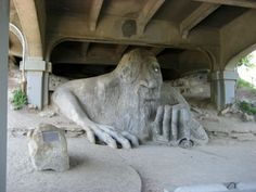 The Fremont Troll is a famous Seattle landmark, both quirky and well known. It's a sculpture of a troll under the bridge holding a VW beetle. The bridge is Rt 99 and the Volkswagon is reall