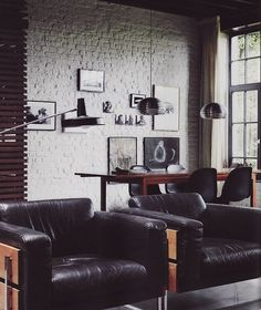 black leather chairs, brick wall, salon style wall - love.