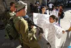 HEBRON : Palestinian children demonstrate near an Israeli check point in the centre of the West Bank city of Hebron after they couldn't pass the checkpoint to get to school as it was closed off by Israeli security forces on August 26, 2014. AFP PHOTO / HAZEM BADER